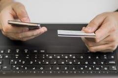 Online-betalning, Man& x27; s-händer som rymmer en kreditkort och använder den smarta telefonen för online-shopping Arkivbild