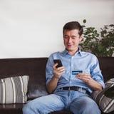 Online-betalning Man som rymmer en kreditkort och använder den smarta telefonen för internetshopping Sale i online-lagret arkivbild