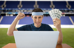 Online betting dollar gaining in stadium. Online betting man and making a lot of dollar in stadium Royalty Free Stock Photos