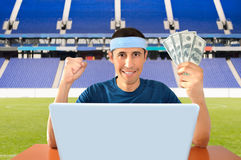Online betting in dollar. Online betting man and making a lot of dollar in the stadium Royalty Free Stock Photo