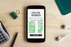 Online bileta pojęcie na mądrze telefonu ekranie na drewnianym biurku Obrazy Stock