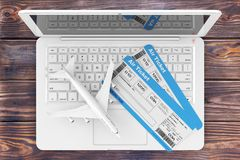 Online Booking Concept. Airline Boarding Pass Tickets with Jet A. Irplane over Laptop on a Wooden Table extreme closeup. 3d Rendering Royalty Free Stock Photos