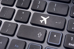 Online booking of flight ticket, with plane sign on keyboard Stock Photos