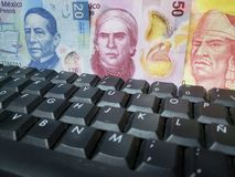 Online business, approach to mexican banknotes and computer keypad. Backdrop for announcements of trading and exchange, bank and commerce, price of buy and sell stock image