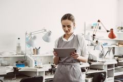 Online business. Close up portrait of young female jeweler in apron holding digital tablet. stock photo