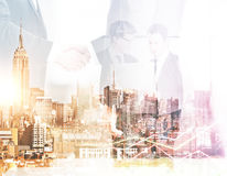 Online business concept. Abstract image of businessmen using laptop and shaking hands on city background. Online business concept. Double exposure Royalty Free Stock Image