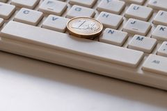 Online business. The concept of on-line sales. Coin in one Euro on the computer keyboard close-up. Spacebar and latin letters. royalty free stock image