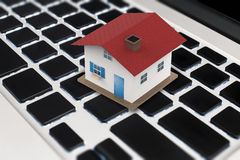 Online business concept with mock up house on keyboard. Online business concept with mock up red roof house on keyboard Royalty Free Stock Image
