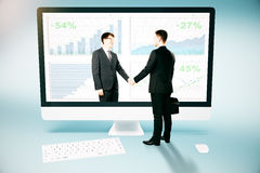 Online business and partnership concept. Businessman shaking hands with abstract digital partner through huge computer screen. Online business and partnership Royalty Free Stock Photography