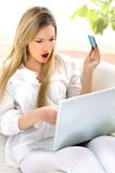 Online with card. Young blond woman with a white laptop and card Stock Image