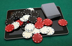 Online card games on tablet. Deck of cards, red, white and black chips on tablet. Onlince casino card games stock photos