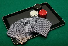 Online card games on tablet. Deck of cards, red, white and black chips on tablet. Onlince casino card games stock image