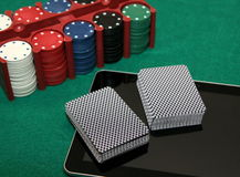Online card games. Two card decks on tablet with chips in bacground stock image