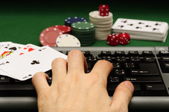 Online casino. Hand on computer keyboard with playing cards chips and dices in background Stock Images