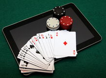 Online casino card games on tablet. Deck of cards, red, white and black chips on tablet. Onlince casino card games stock photography