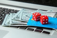 Online casino, online gambling. Money cash dollars and credit brief with dice for gaming on laptop keyboard. royalty free stock photo