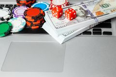 Online casino laptop. Laptop keyboard and chips with dice and money cash dollars on green gaming table. Game addiction gambling. Poker online stock image