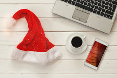 Online christmas holiday shopping concept. Santa claus red hat next to computer keyboard and cup of coffee royalty free stock photography