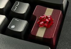 Online christmas shopping concept. Red computer enter key wrapped with a gold gift ribbon and bow Royalty Free Stock Images