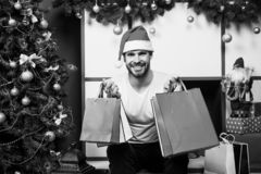 Online christmas shopping. New year scene with tree and gifts. man in santa hat hold christmas present. happy santa man