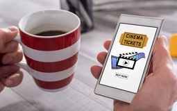 Online cinema tickets booking concept on a smartphone. Male hand holding a smartphone with online cinema tickets booking concept Stock Image