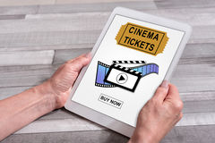 Online cinema tickets booking concept on a tablet. Female hands holding a tablet with online cinema tickets booking concept Royalty Free Stock Photography