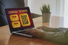 Man buying cinema tickets at home with a laptop on the internet. Royalty Free Stock Photos