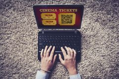 Woman buying cinema tickets on the internet with a laptop computer. Royalty Free Stock Photography