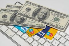 Online Commerce, Ecommerce, credit and debit cards with dollars and a keyboard. Stock Image