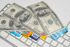 Online Commerce, Ecommerce, credit and debit cards with dollars and a keyboard. Stock Images