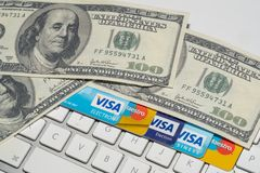 Online Commerce, Ecommerce, credit and debit cards with dollars and a keyboard. Royalty Free Stock Image