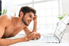 Online communication evokes interest in everyone. Carefree young man is communicating in internet with aspiration. He is lying on bed and laughing Stock Image
