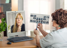 Online consultation of orthodontist. Mature female dentist examining young women during internet video session.  Virtual doctor in white uniform looks at x-ray Stock Images