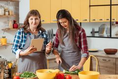 Online cookery class home cooking family hobby. Online cookery class. Home cooking. Women family hobby. Mother and daughter watching food recipe tutorial video stock photography