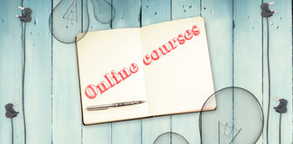 Online courses against notepad and bulbs on wooden background Royalty Free Stock Images