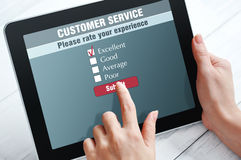 Online customer service. Satisfaction survey on a digital tablet Royalty Free Stock Images
