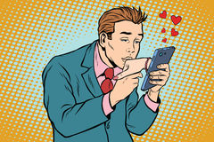 Online date and love a man kisses a womans hand via smartphone. Pop art retro vector illustration Royalty Free Stock Image
