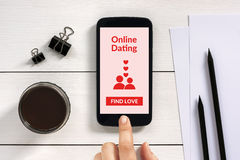 Online dating app mock up on smart phone screen with office obje Royalty Free Stock Photos