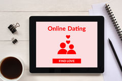 Online dating app mock up on tablet screen with office objects. On white wooden table. All screen content is designed by me Royalty Free Stock Photos