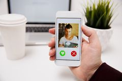 Online dating app in smartphone. looking at photo of beautiful royalty free stock image