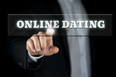 Online dating. Button on virtual screen with male hand activating it from behind Stock Image