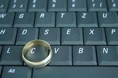 Online dating and cheating. Keyboard with the word sex spelled on it and a wedding ring Royalty Free Stock Photos