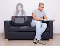 Online dating concept - handsome man sitting on sofa and chattin Stock Photo