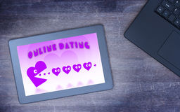 Online dating on a tablet. Concept of love, purple pacman eating hearts Royalty Free Stock Photography