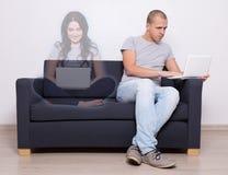 Online datowanie pojęcie - przystojny mężczyzna obsiadanie na kanapie i chattin zdjęcie stock