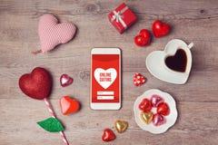 Online-datummärkningbegrepp med smartphoneåtlöje övre och hjärtachoklader Valentin beröm för dagromantiker Arkivbilder