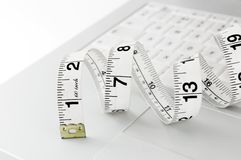 Online dieting. Measuring tape sitting on the keyboard of a white laptop Royalty Free Stock Image