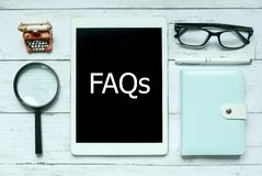Online digital FAQs Frequently Asked Questions concept. Top view of magnifying glass,notebook,pen,glasses and tablet written with. FAQs on white wooden royalty free stock photography