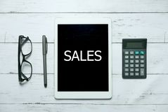 Online digital sales commerce business technology concept. Top view of glasses,calculator,pen and tablet written with Sales on. White wooden background royalty free stock images