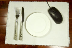 Online Dinner Reservation, Review or Ordering Concept. Placemat with knife, fork, plate and computer mouse representing internet or online restaurant review Stock Images